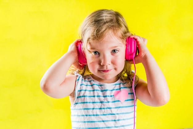 Het grappige leuke blonde peutermeisje luistert muziek met heldere roze hoofdtelefoons