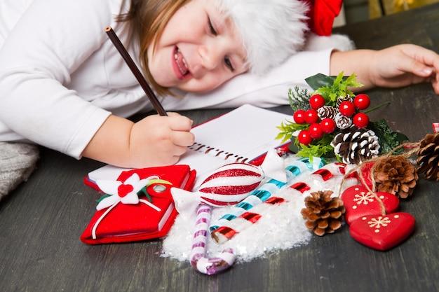 Het grappige meisje in kerstmanhoed schrijft brief aan kerstman dichtbij kerstmis de