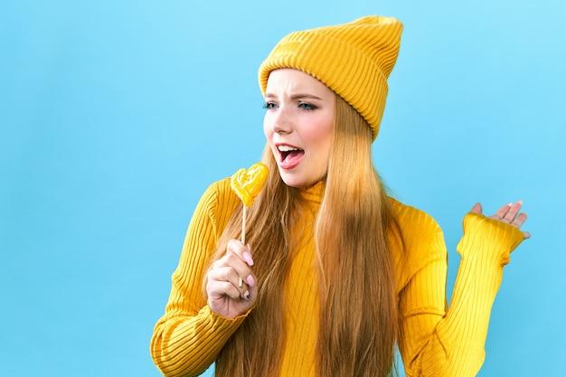 Het grappige meisje met lang haar dat pret heeft, het glimlachen, zingt tegen blauwe muur. meisje gek rond. karaoke concept, slow motion.