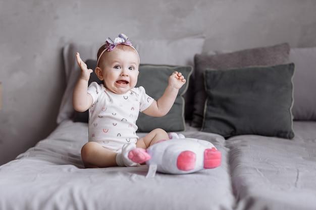 Het grappige meisje speelt thuis met stuk speelgoed eenhoorn op bed. concept van kinderdag. gelukkige baby's, familiedag
