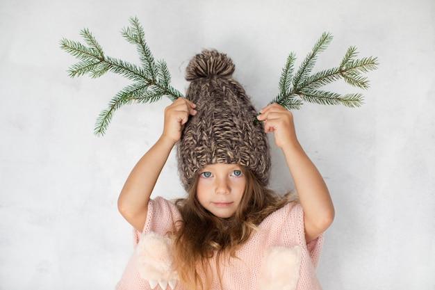 Het grappige meisje stellen met de winterhoed