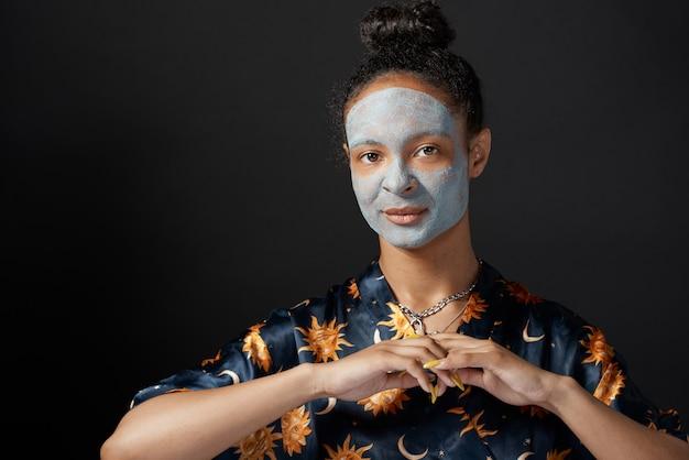 Het grappige meisje van yong met het masker van de kleischoonheid op huid geïsoleerd model