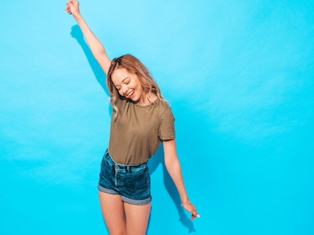 Het grappige model stellen dichtbij blauwe muur in studio. heft haar handen op