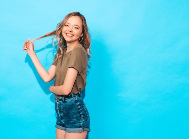 Het grappige model stellen dichtbij blauwe muur in studio. zij raakt haar haar