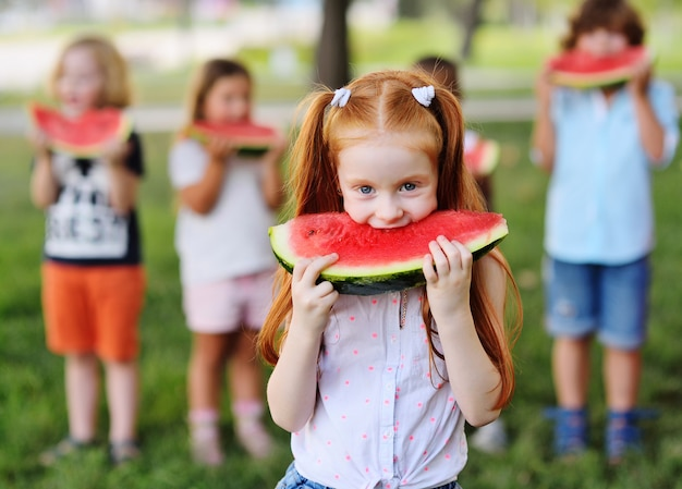 Het grappige roodharige meisje eet greedily sappige rijpe watermeloen