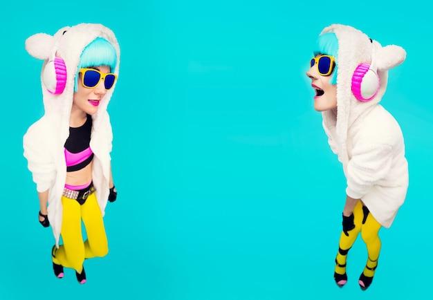 Het grappige sweatshirt van dj girls teddybeer op een blauwe achtergrond die aan muziek luistert. gek winterfeest