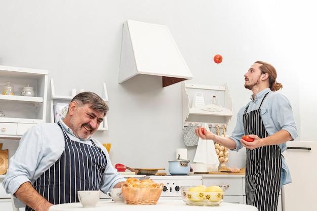 Het grappige zoon jongleren met met tomaten