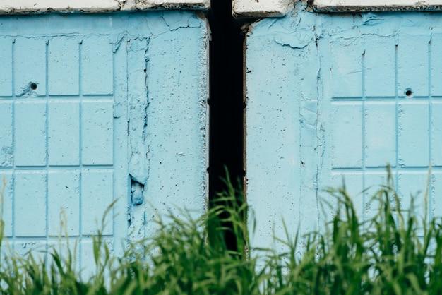Het gras groeit van muur van blauwe rechthoektegels dicht omhoog. groen gazon voor de bouw van muur met kopie ruimte. patroon met aard en bouw.