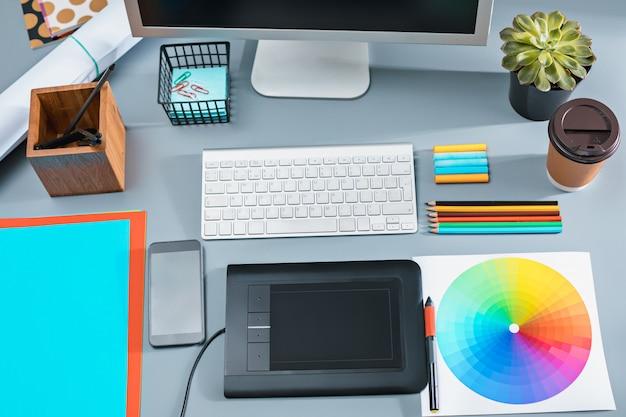 Het grijze bureau met laptop, notitieblok met blanco vel, bloempot, stylus en tablet om te retoucheren