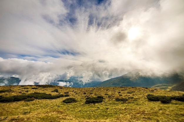 Het groene bergenpanorama op blauwe hemel met witte wolken kopieert ruimteachtergrond op heldere zonnige dag. toerisme en reizen concept.