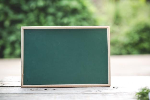 Het groene bord is leeg voor het plaatsen van tekst op de houten vloer.
