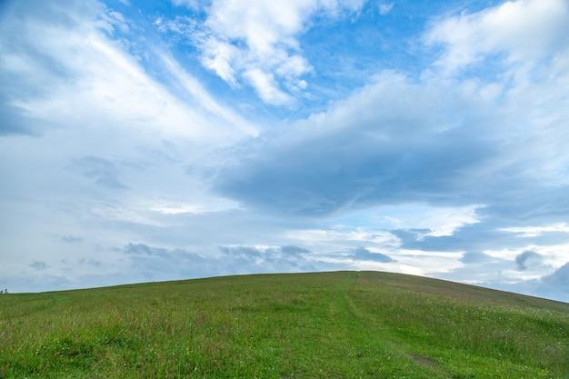 Het groene landschap van grasheuvels in de zomer tegen blauwe hemel en mooie witte wolken.