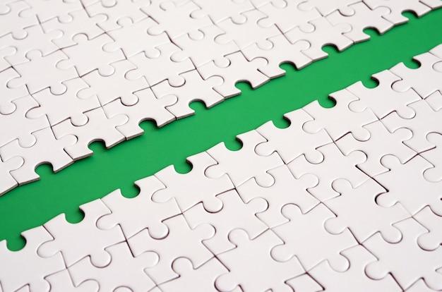 Het groene pad wordt op het platform van een witgevouwen puzzel gelegd
