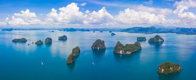 Het groene weelderige tropische eiland van thailand in een blauwe en turkooise overzees met eilanden op de achtergrond en de wolken