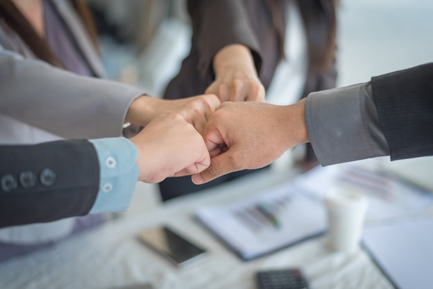 Het groepswerk sluit zich aan bij handen, close-up van partners die stapel van handen maken op vergadering, bedrijfsconcept