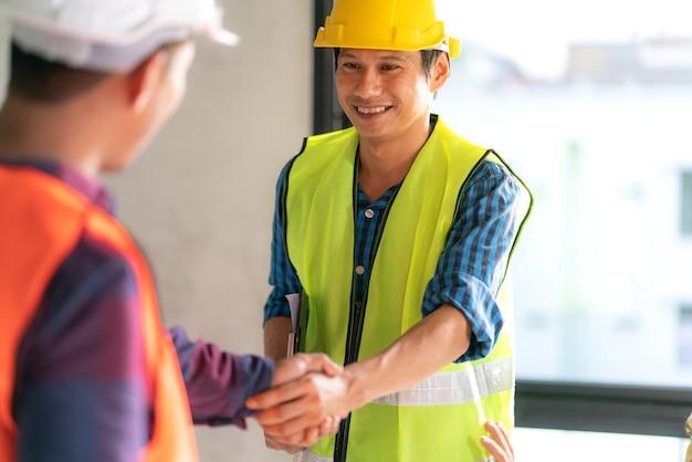 Het groepswerk van de ambtenaar is gelukkig en schudt handen om in de bouwconstructie van het succeshuis te vieren