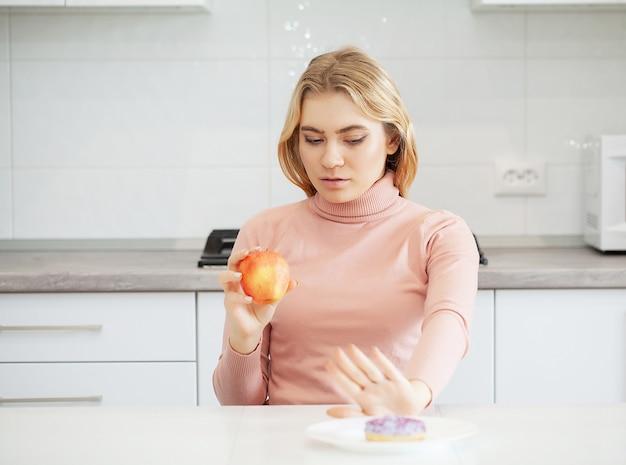 Het grote model maakt een keuze voor gezond eten en fruit door fast food te weigeren