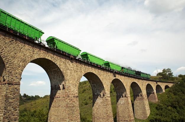 Het grote spoorviaduct gemaakt van bakstenen en de trein rijdt er langs