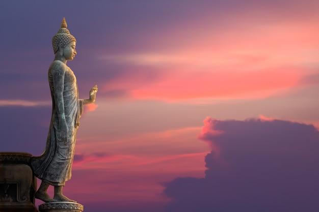 Het grote standbeeld van boedha op zonsonderganghemel