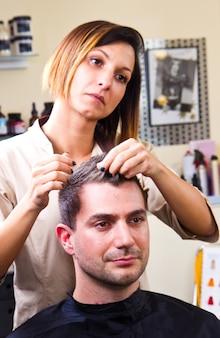 Het haar van de gelukkige vrouwelijke herenkapper het plaatsen cliënt