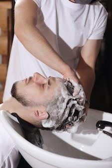 Het haar van een man wassen voor een knipbeurt in een salon