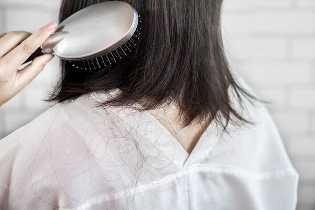 Het haarverlies van de vrouw na het gebruik van haarborstel