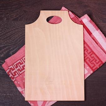 Het hakbord op een rode keukenhanddoek ligt.