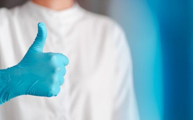 Het handgebaar van arts die blauwe handschoenen dragen, ondertekent voorgoed