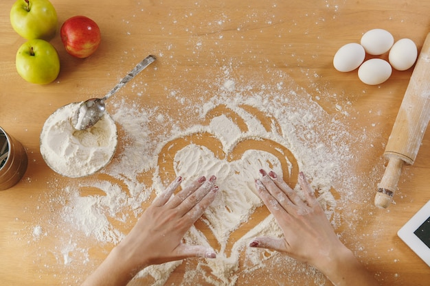 Het handgetekende hart in bloem op de keukentafel en andere ingrediënten. bovenaanzicht.