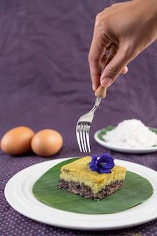 Het handvat van een vork die op het punt staat om het dessert van zwarte plakkerige rijst met custard op het bananenblad te plaatsen.