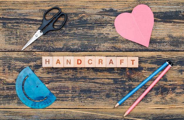 Het handwerk en het hobbyconcept met houten kubussen, hulpmiddelen, snijden hartdocument op houten vlakte als achtergrond lagen.