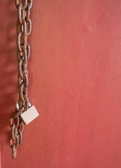Het hangslot met oude ketting op de rode houten deur