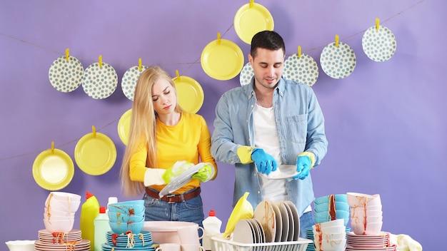 Het hardwerkende echtpaar, vrouw en man staan bij een tafel met een stapel vuile vaat