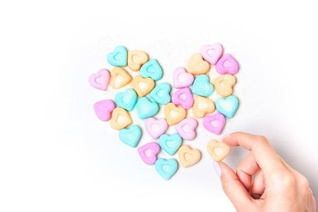 Het hart is bekleed met stukjes suiker op een witte achtergrond. het meisje houdt suiker vast. liefdesymbool voor valentijnsdag
