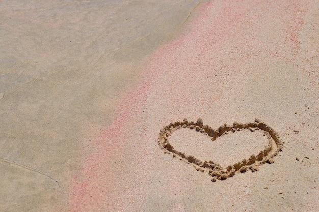 Het hart is geschilderd op het gekleurde zand op een tropisch strand.