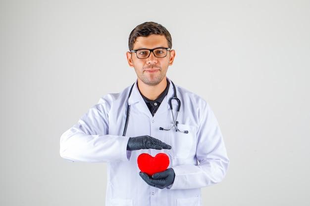 Het hart van de artsenholding in witte laag met stethoscoop en het kijken positief,