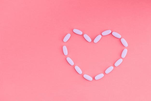 Het hart wordt blootgesteld met witte pillen op een roze achtergrond. medische concept. plat leggen