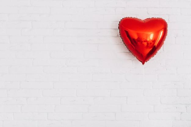 Het hartballon van nice dichtbij witte muur