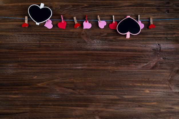 Het hartschoolbord van valentijnskaarten met rode harten op bruine houten achtergrond