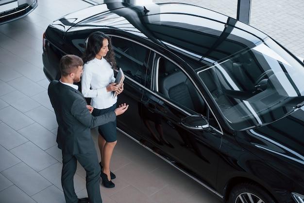 Het heeft enkele speciale functies. vrouwelijke klant en moderne stijlvolle bebaarde zakenman in de auto-salon