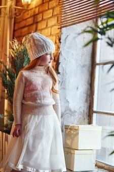 Het heldere roodharige meisje in een witte hoed en een mooie jurk zit in een herfstcafé. roodharige meisje met grote blauwe ogen en een mooie trui voldoet aan de lente