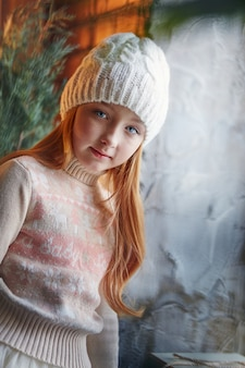 Het heldere roodharige meisje in een witte hoed en een mooie jurk zit in een herfstcafé. roodharigevrouw met grote blauwe ogen en een mooie sweater ontmoet de lente