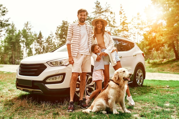 Het hele gezin kwam een weekend naar de natuur. pappa en mamma met hun dochter en een labrador-hond staan bij de auto. vrije tijd, reizen, toerisme.
