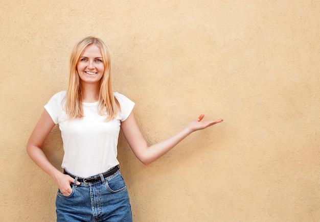 Het hipstermeisje die lege witte t-shirt dragen en jeans die tegen ruwe straatmuur stellen, minimalistische stedelijke kledingsstijl, vrouw toont met de hand