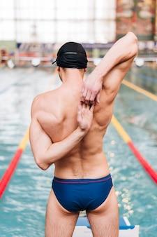 Het hoge hoek mannelijke uitrekken zich alvorens te zwemmen