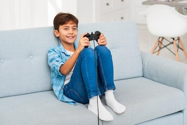 Het hoge hoekjongen spelen met joystick