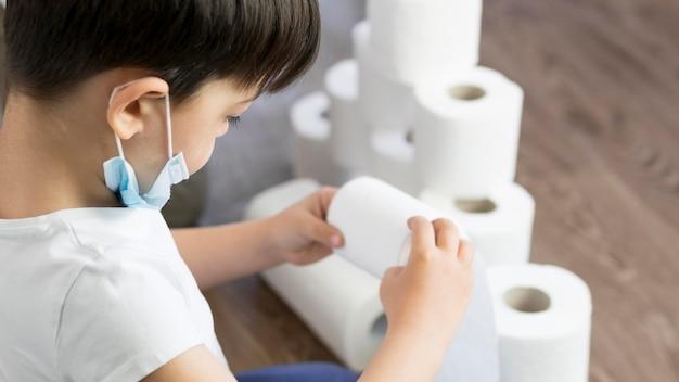 Het hoge hoekjongen spelen met toiletpapier