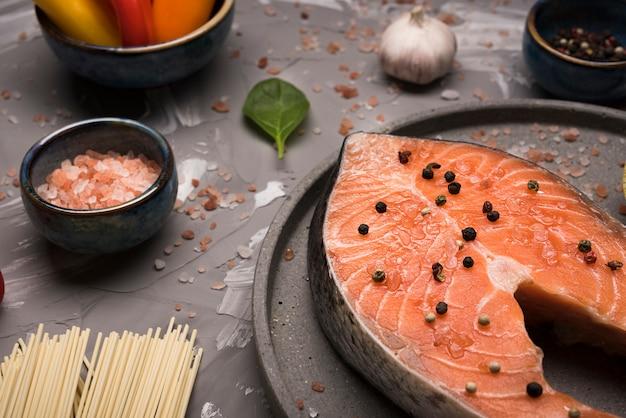 Het hoge lapje vlees van de hoek ruwe zalm op dienblad met ingrediënten