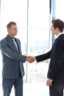 Het hogere en ondergeschikte zakenman schudden overhandigt overeenkomst