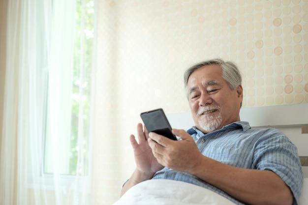 Het hogere mannetje die een smartphone, het glimlachen met behulp van voelt thuis gelukkig gelukkig in bed - levensstijl hoger concept